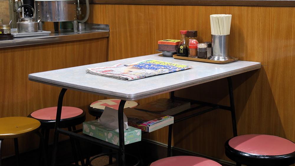 테이블 위에는 신문이, 아래에는 휴지와 잡지가 있습니다.